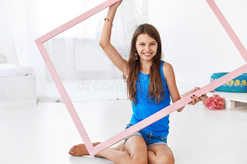 Mooi meisje die een kader en het glimlachen houden stock afbeeldingen