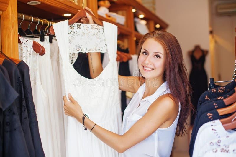 Mooi meisje die een kleding voor huwelijk kiezen stock foto's