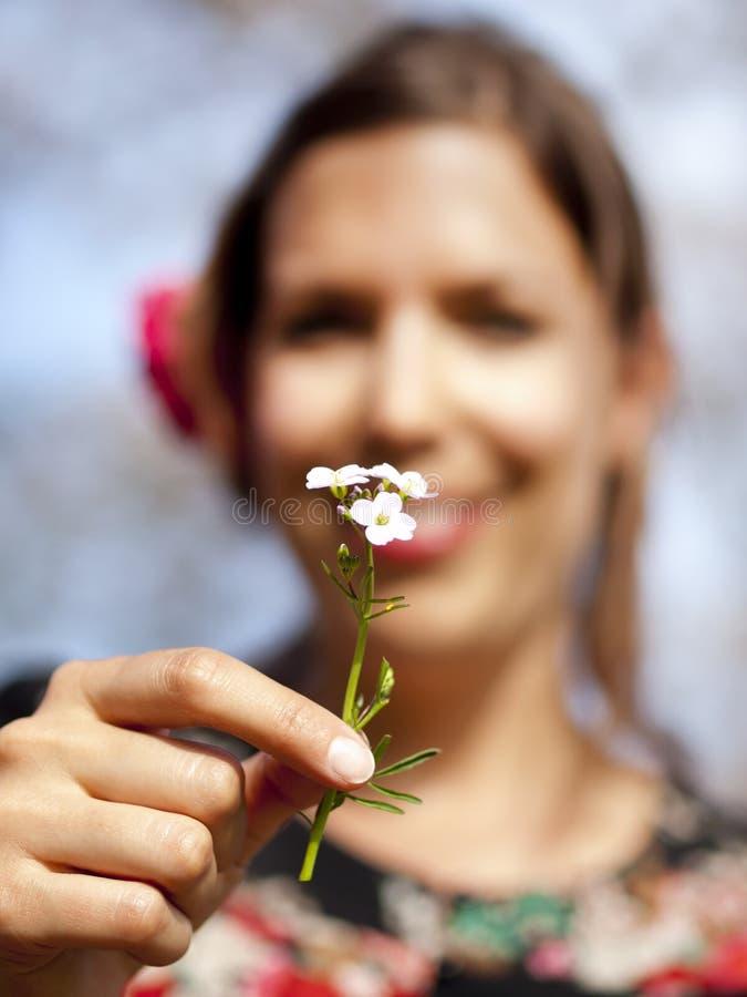 Mooi meisje die een koekoeksbloem in de lente overhandigen stock afbeelding