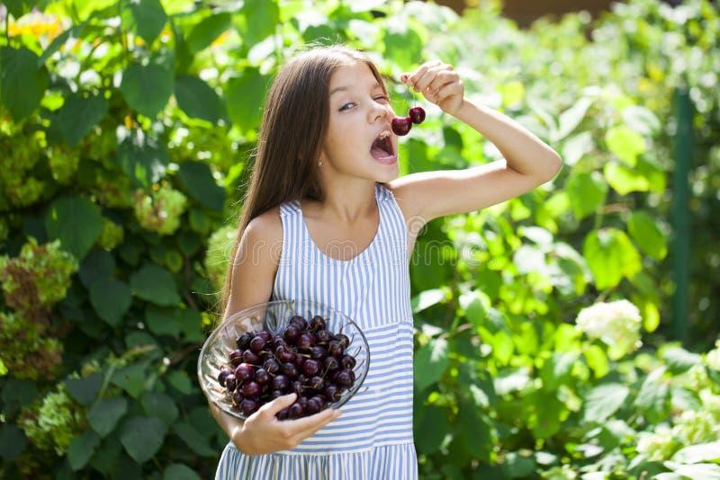 Mooi meisje die een kom van kersen in de tuin houden royalty-vrije stock foto's