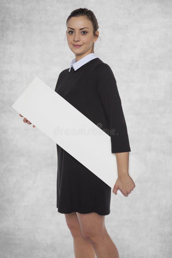 Mooi meisje die een leeg aanplakbord dichtbij houden stock afbeelding