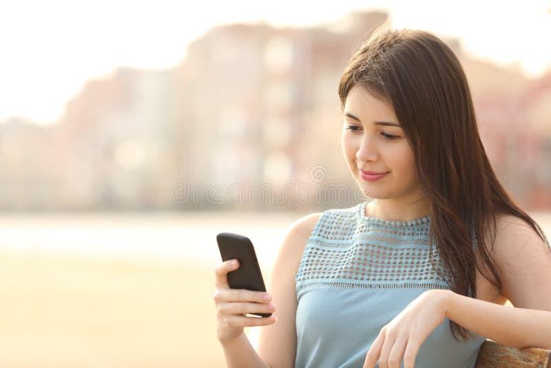 Mooi meisje die een mobiele telefoon in een stedelijk park met behulp van stock afbeelding