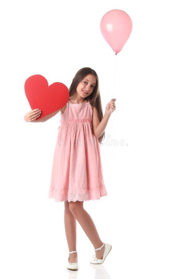 Mooi meisje die een rode hartvorm en een roze ballon houden stock foto's