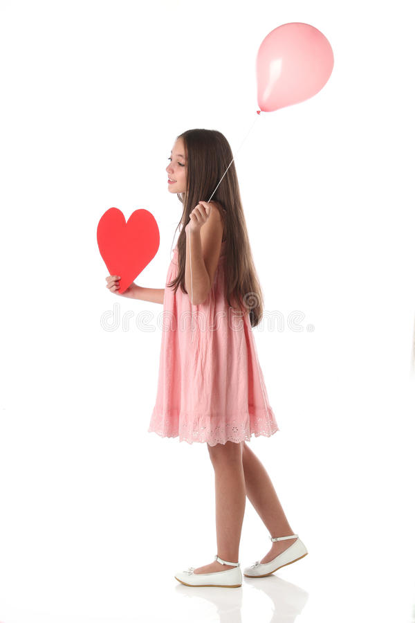 Mooi meisje die een rode hartvorm en een roze ballon houden stock fotografie