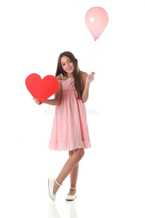 Mooi meisje die een rode hartvorm en een roze ballon houden royalty-vrije stock fotografie