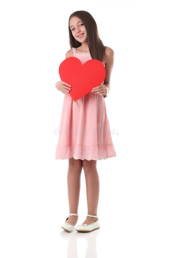 Mooi meisje die een rode hartvorm, over witte achtergrond houden stock foto's