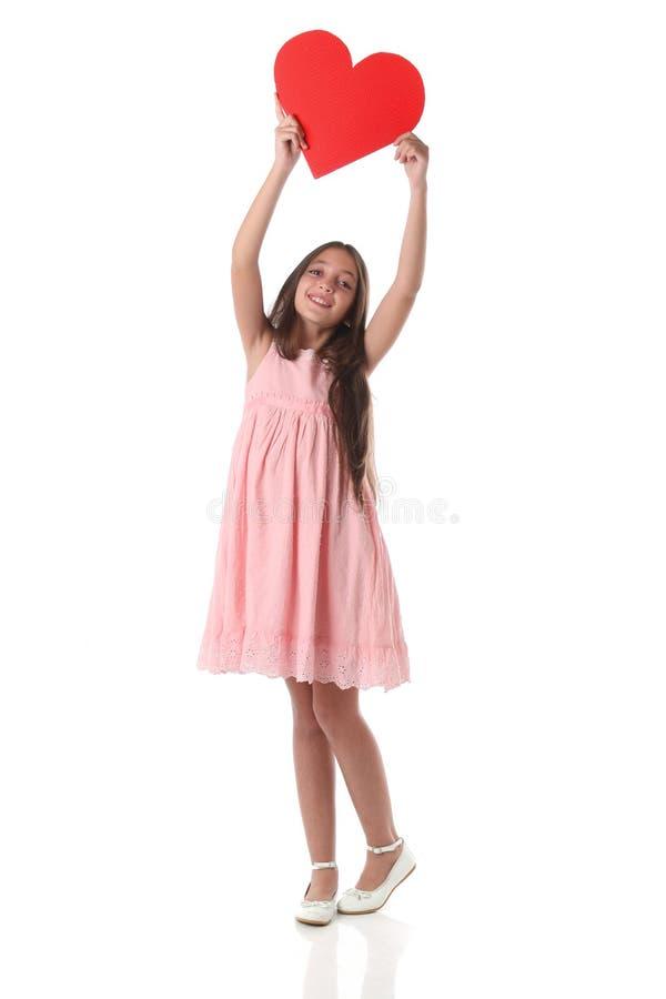 Mooi meisje die een rode hartvorm, over witte achtergrond houden stock foto