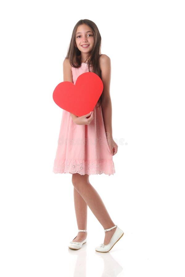 Mooi meisje die een rode hartvorm, over witte achtergrond houden royalty-vrije stock afbeeldingen