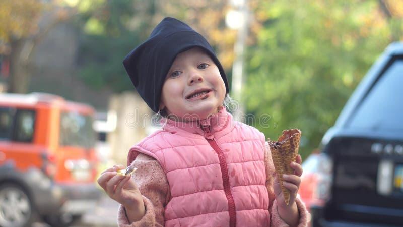 Mooi meisje die een roomijs in openlucht en glimlachen eten royalty-vrije stock fotografie