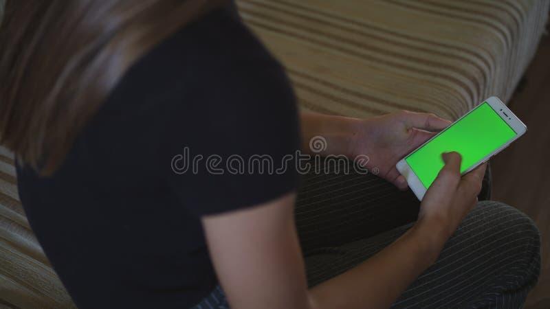 Mooi meisje die een smartphone in de handen van het groen het scherm groen scherm houden, hand van de mens die mobiele smartphone royalty-vrije stock foto's