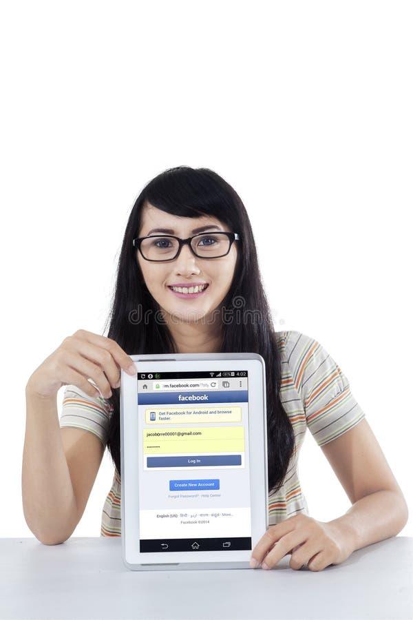 Mooi meisje die facebook profiel op tablet tonen stock foto