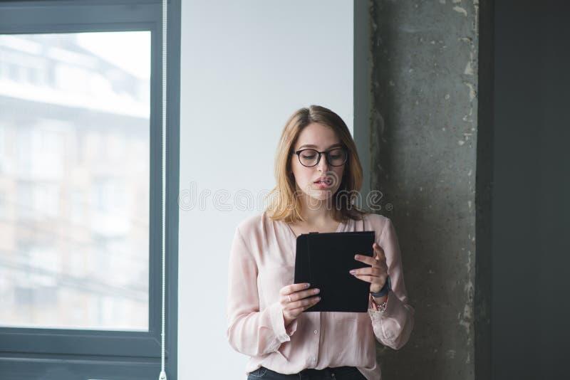 mooi meisje die glazen in de glazen dragen bij het venster in het bureau royalty-vrije stock foto