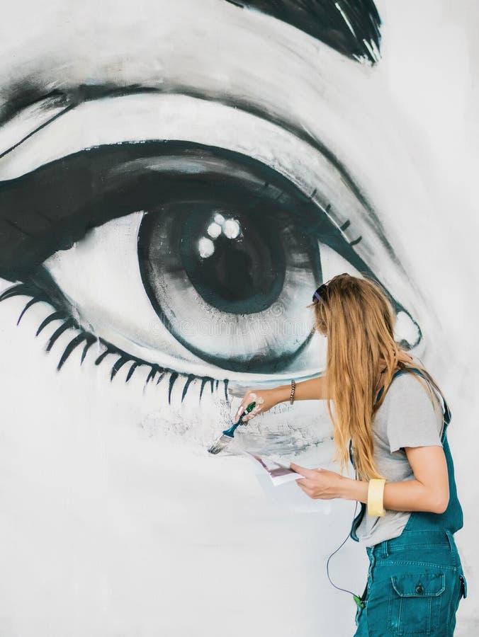 Mooi meisje die graffiti van groot vrouwelijk gezicht met aërosolnevel maken op stedelijke straatmuur Creatief art begaafd stock foto's