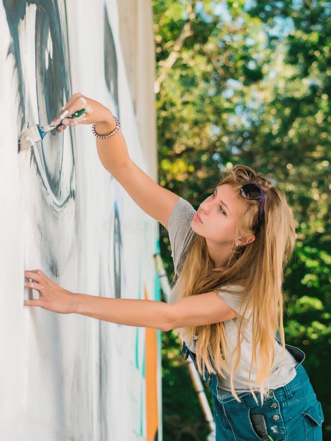 Mooi meisje die graffiti van groot vrouwelijk gezicht met aërosolnevel maken op stedelijke straatmuur Creatief art begaafd stock fotografie