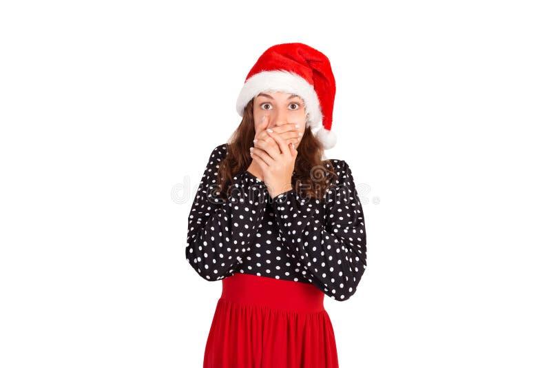 Mooi meisje die haar mond behandelen emotioneel meisje in Kerstmishoed van de Kerstman dat op witte achtergrond wordt geïsoleerd  stock foto's