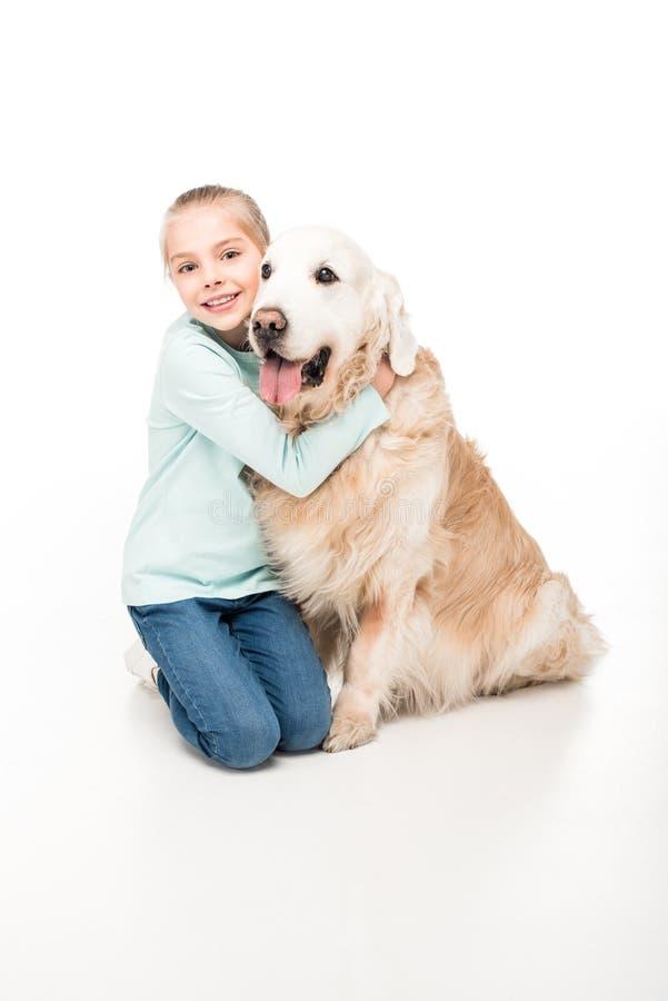 mooi meisje die hond koesteren en bij camera glimlachen stock afbeelding