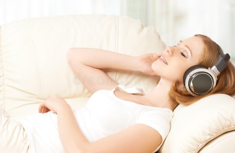 Mooi meisje die in hoofdtelefoons van muziek thuis genieten stock afbeelding