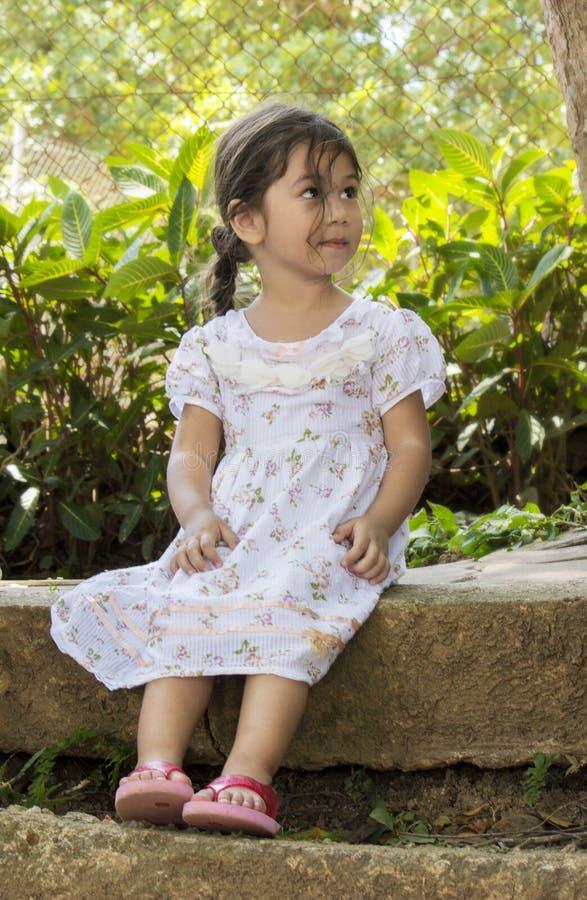 Mooi meisje die iets bekijken terwijl het zitten op de concrete rand van een openbare tuin royalty-vrije stock foto's