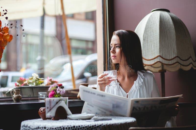 Mooi meisje die kop van koffie hebben en krant lezen stock fotografie
