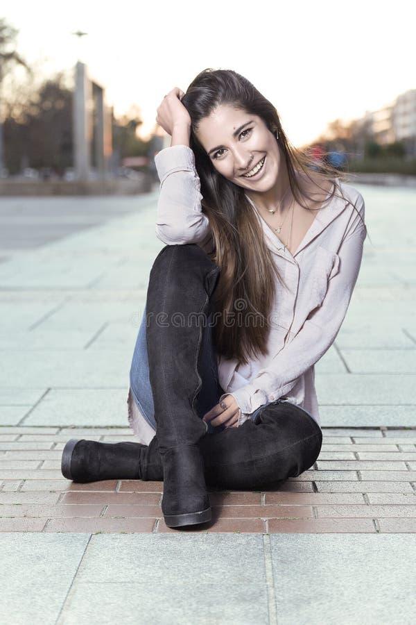 Mooi meisje die in laarzen op de vloer zitten royalty-vrije stock foto's