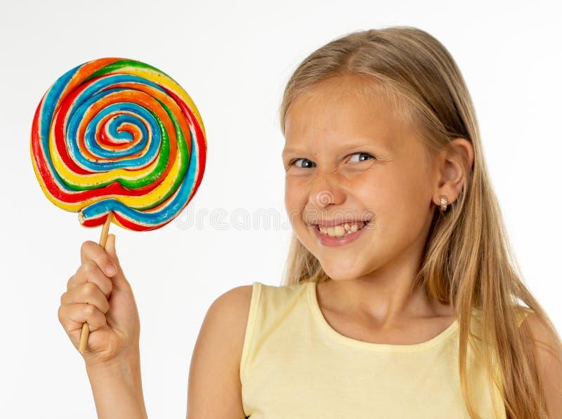 Mooi meisje die lolly op witte achtergrond eten stock foto