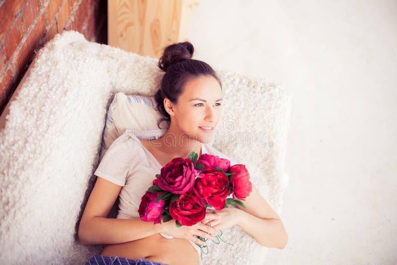 Mooi meisje die met een boeket van bloemen liggen royalty-vrije stock afbeeldingen
