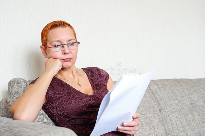 Mooi meisje die met glazen door belastingsdocumenten kijken Emotie van concentratie Ernstige verordeningen royalty-vrije stock foto