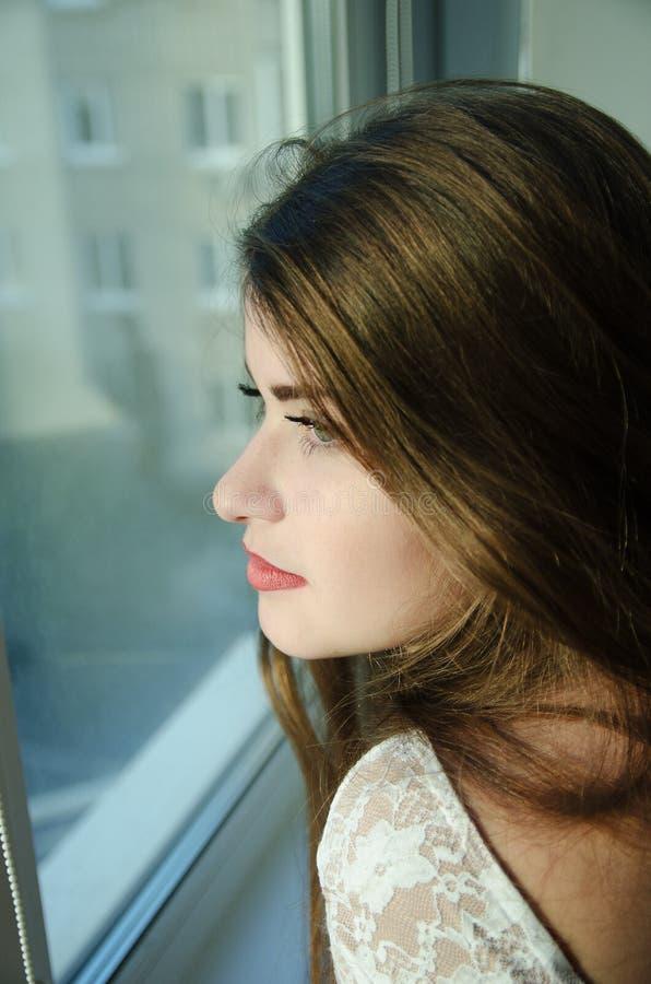 Mooi meisje die met lang bruin haar in het venster kijken stock foto