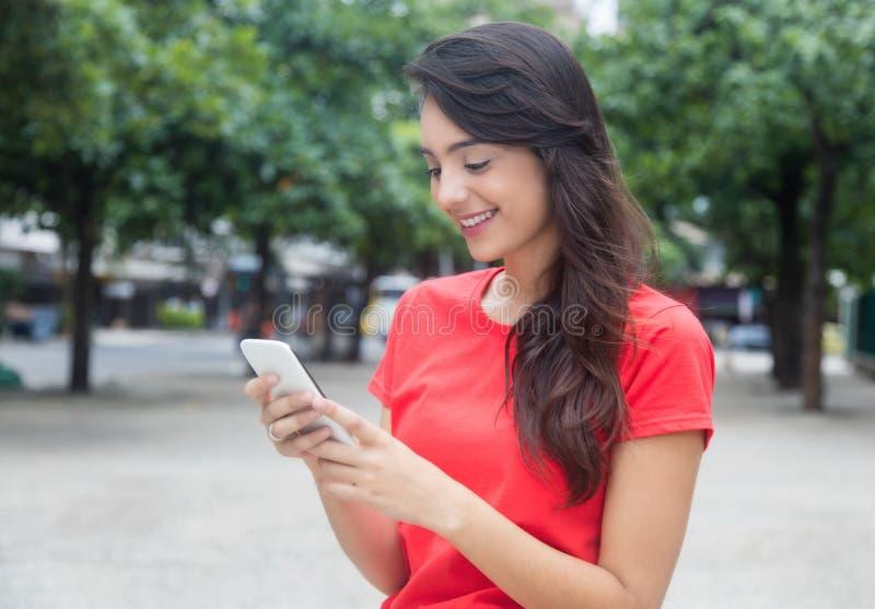 Mooi meisje die met rood overhemd het net met telefoon surfen royalty-vrije stock afbeelding