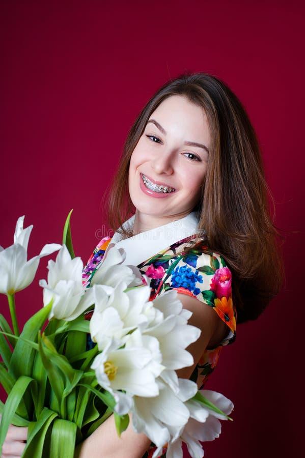Mooi meisje die met steunen witte tulpen houden stock fotografie