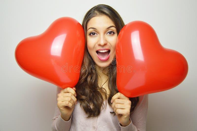 Mooi meisje die met Valentine-hartballons opgewekt de camera bekijken Zoete jonge vrouw met twee hart gevormde ballons op wit royalty-vrije stock foto