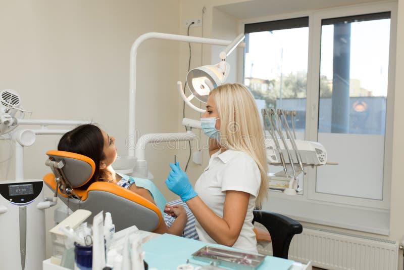 Mooi meisje die mondcontrole in het ziekenhuis door professionele vrouwelijke tandarts hebben royalty-vrije stock foto's