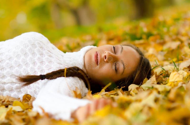 Mooi meisje die op de herfstbladeren liggen royalty-vrije stock foto