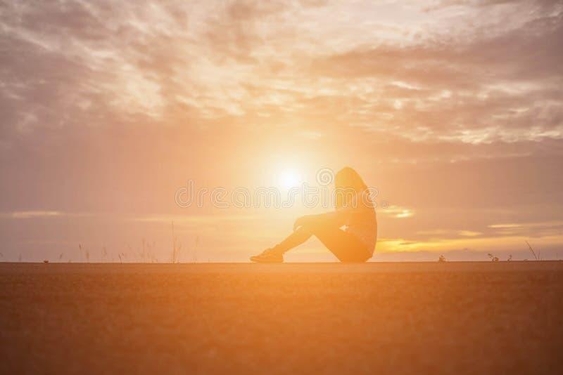 Mooi meisje die op de mooie zonsondergang op het water letten stock afbeelding