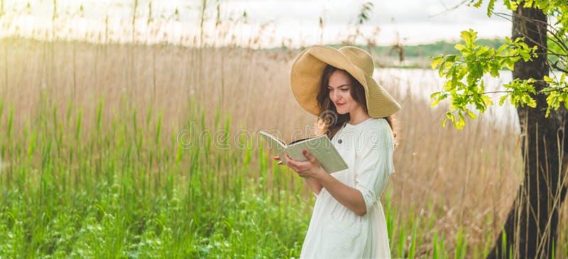 Mooi meisje die op gebied een boek lezen De meisjeszitting op een gras, lezing een boek Rust en lezing stock fotografie