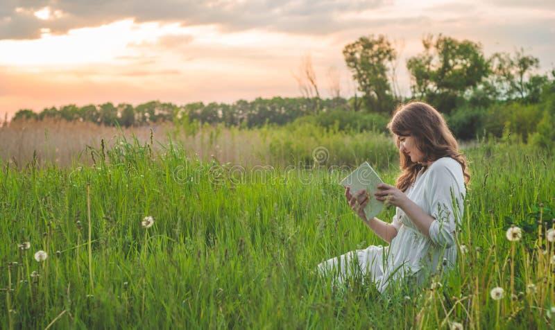 Mooi meisje die op gebied een boek lezen De meisjeszitting op een gras, lezing een boek Rust en lezing royalty-vrije stock fotografie