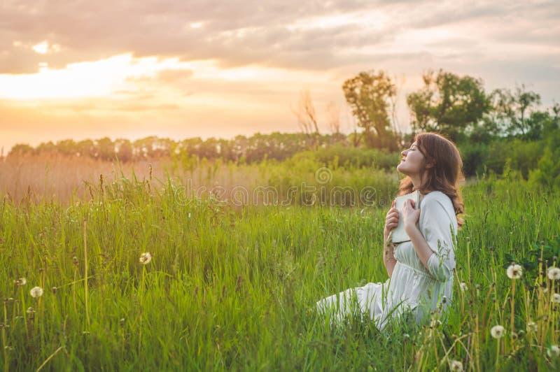 Mooi meisje die op gebied een boek lezen De meisjeszitting op een gras, lezing een boek Rust en lezing stock afbeelding