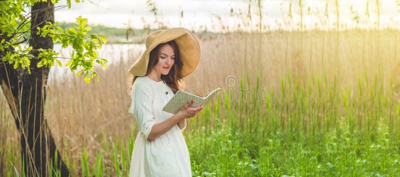 Mooi meisje die op gebied een boek lezen De meisjeszitting op een gras, lezing een boek Rust en lezing royalty-vrije stock foto