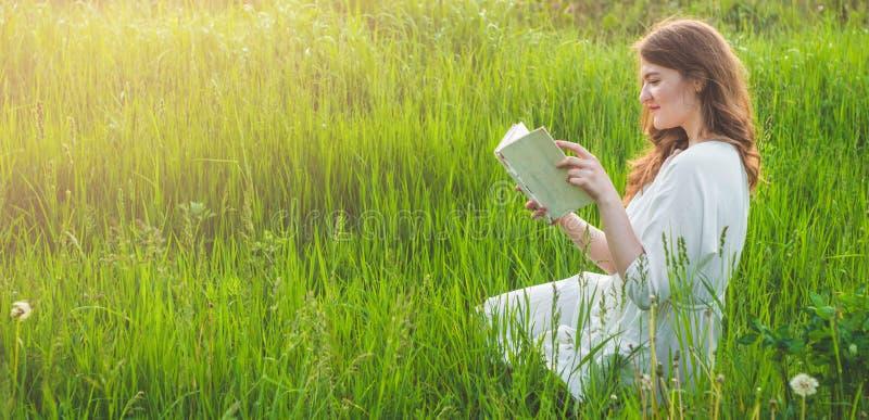 Mooi meisje die op gebied een boek lezen De meisjeszitting op een gras, lezing een boek Rust en lezing stock foto