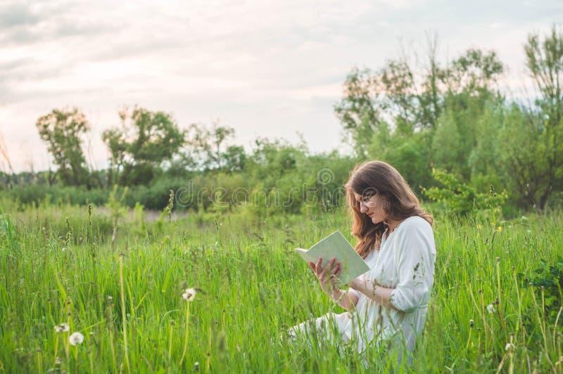 Mooi meisje die op gebied een boek lezen De meisjeszitting op een gras, lezing een boek Rust en lezing stock afbeeldingen
