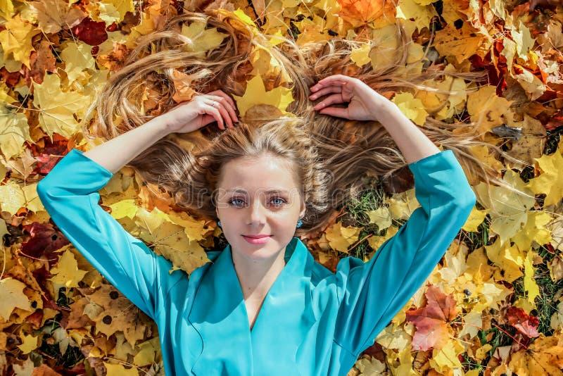 Mooi meisje die op gras met esdoornbladeren in de herfst liggen royalty-vrije stock afbeeldingen