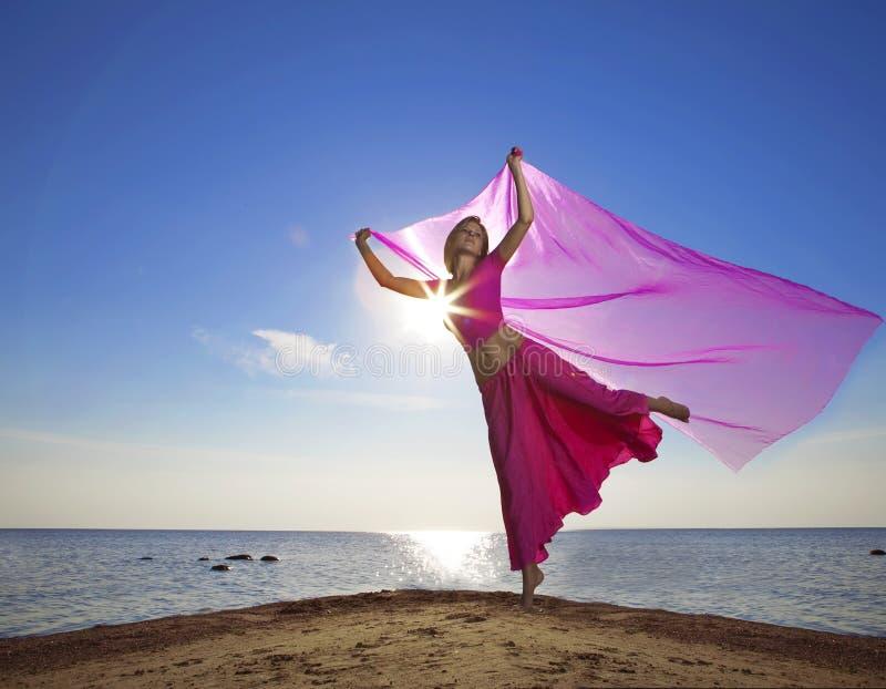 Mooi meisje die op het strand bij zonsondergang springen stock foto's