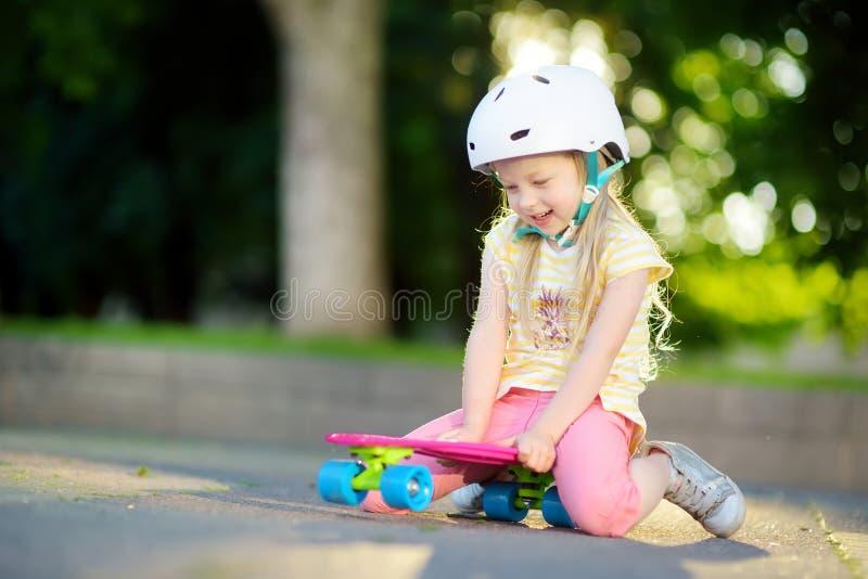 Mooi meisje die op mooie de zomerdag in een park leren met een skateboard te rijden Kind genieten die rit in openlucht met een sk royalty-vrije stock afbeeldingen