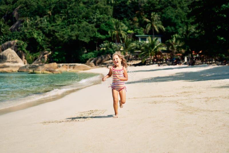 Mooi meisje die op oceaanstrand in tropisch eiland lopen royalty-vrije stock foto