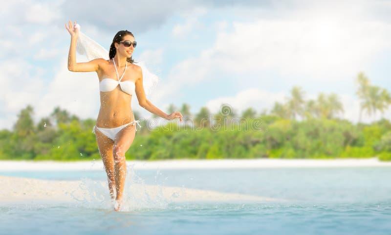 Mooi meisje die op tropisch strand lopen stock fotografie