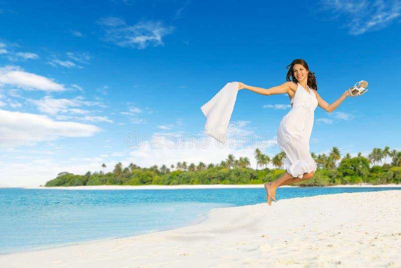 Mooi meisje die op tropisch strand springen stock fotografie