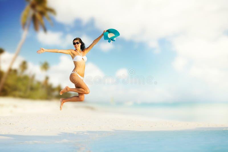 Mooi meisje die op tropisch strand springen royalty-vrije stock foto