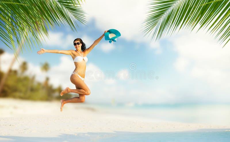 Mooi meisje die op tropisch strand springen stock foto