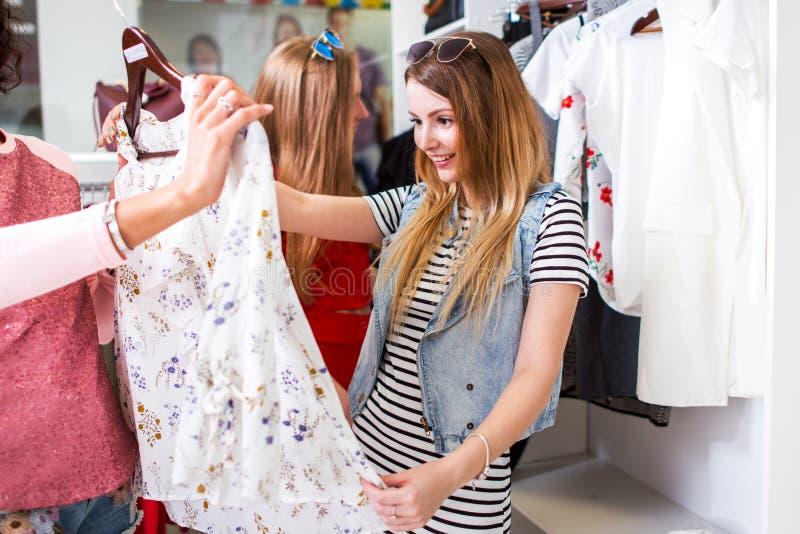 Mooi meisje die opgewekt die houdend blouse kijken door winkelende medewerker in kledingsopslag wordt aangeboden royalty-vrije stock foto
