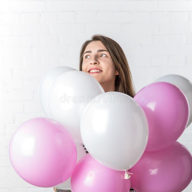 Mooi meisje die over bos van ballons op witte baksteen glimlachen stock fotografie